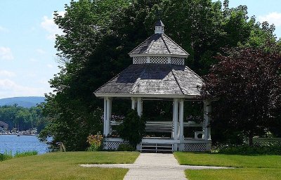 A photo of a white gazebo on a grassy lawn