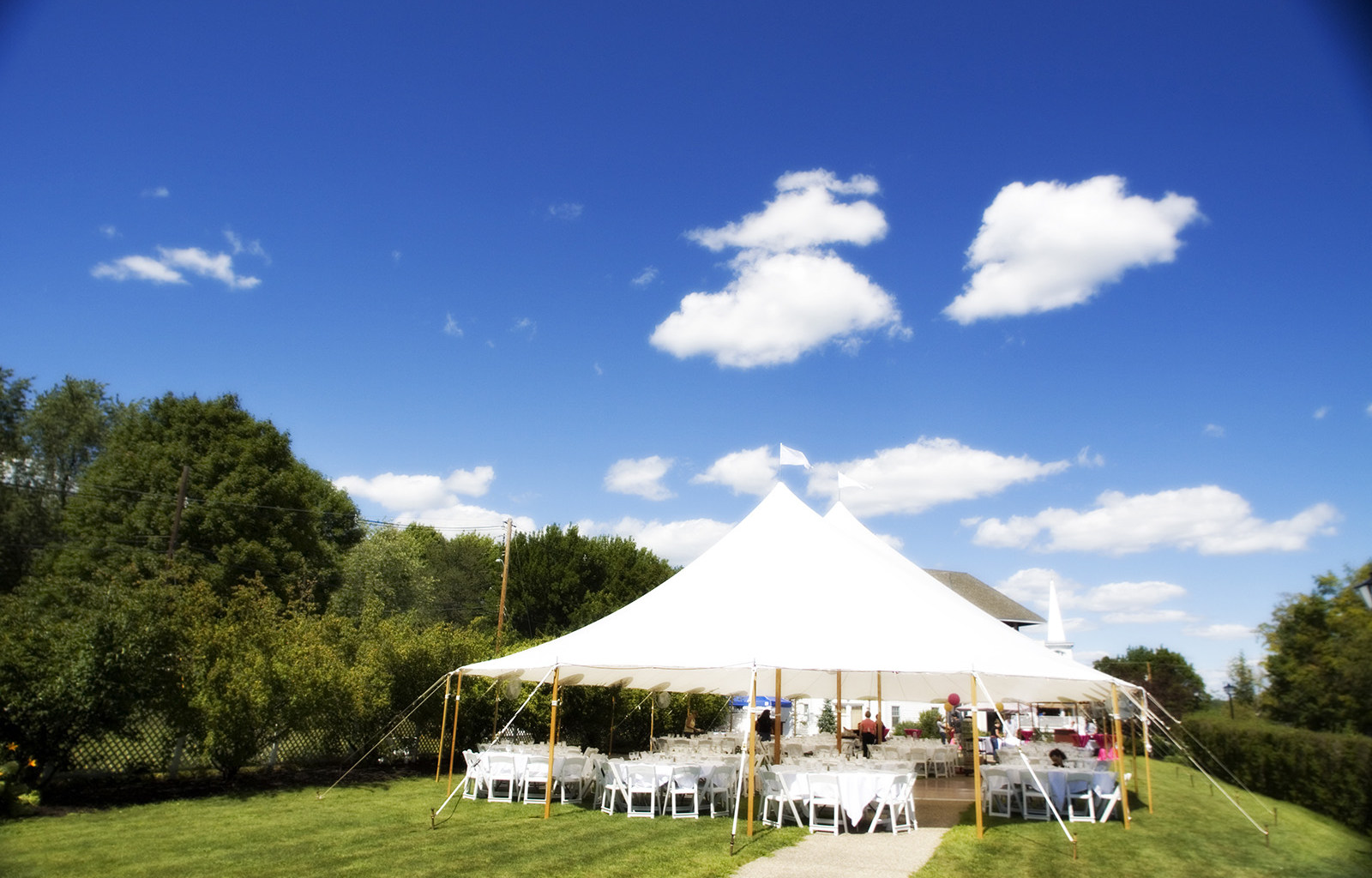 A photo of a large white tent on a grassy lawn with tables and chairs set up underneath