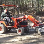 a man operating an orange tractor