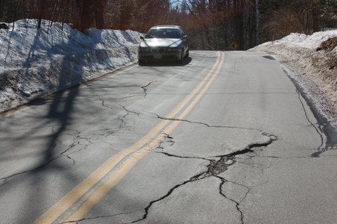 a road with cracks in it. There's snow off the side and a car driving in the opposite direction.