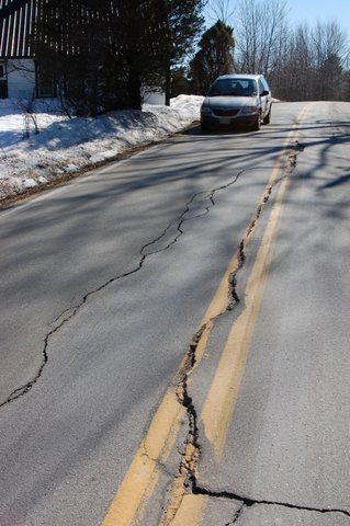 A road with a large crack down the middle, snow off to the side and a car on the opposite side of the road.