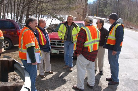 a group of men in yellow and orange safety jackets having a meeting outside surrounded by vehicles.