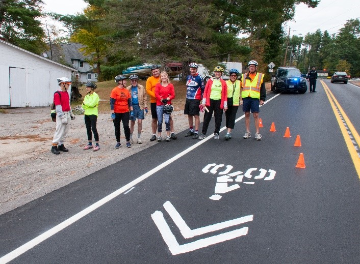 An image of a road shoulder, showing the new cyclist markings on the road. Several people in cycling gear stand nearby.