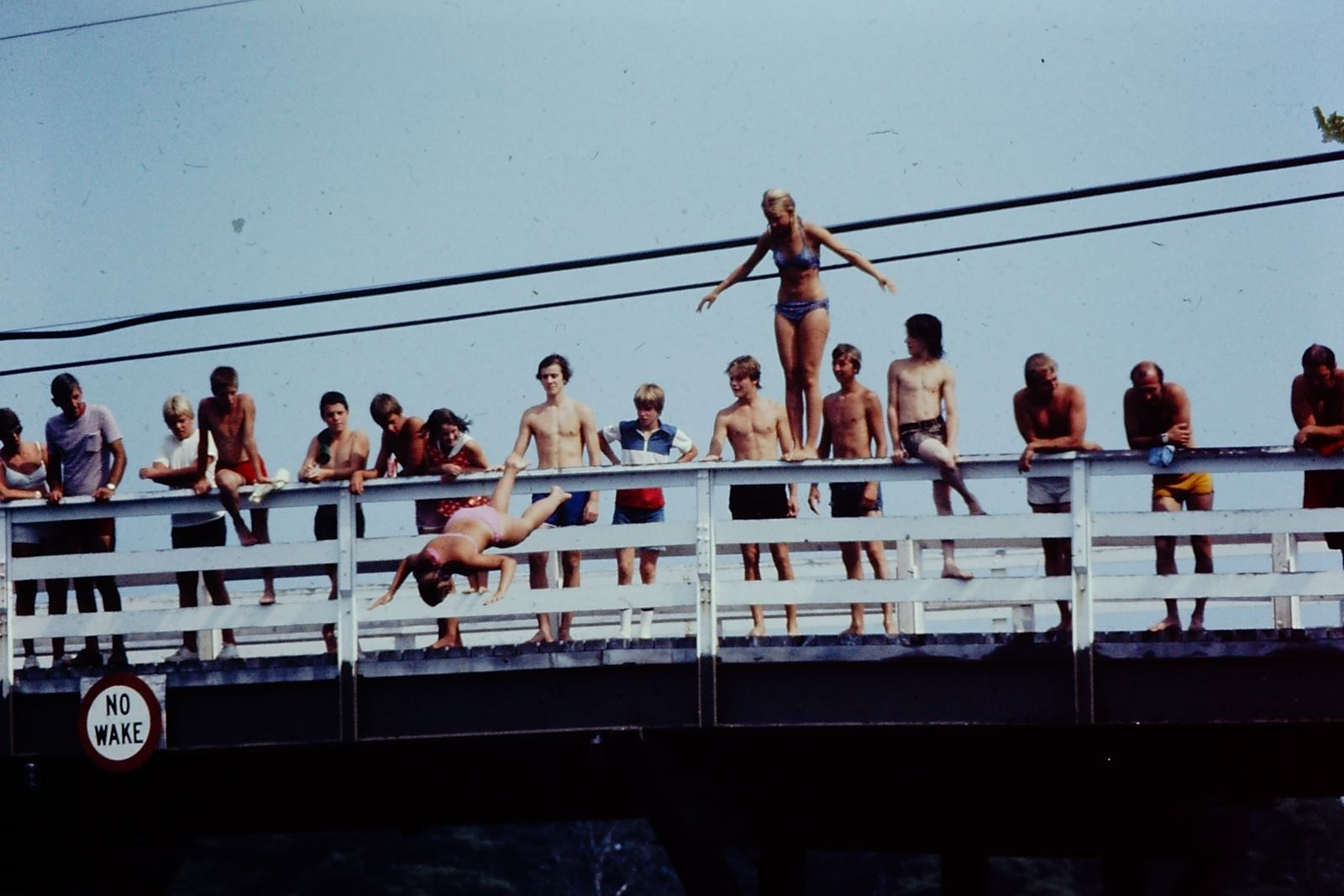 A photo of children and teenagers lined up along the side of a bridge, one girl in a swimsuit has jumped off and is diving towards the water, another is standing on the railing waiting her turn.