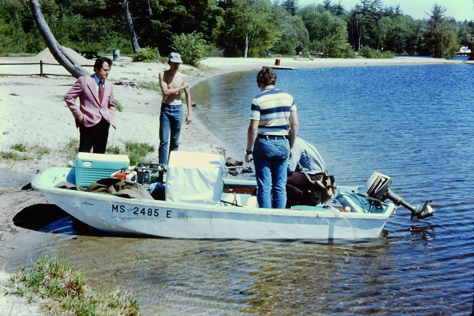 A photo of a small white boat at the edge of a lake, loaded with equipment,  with three men standing by it