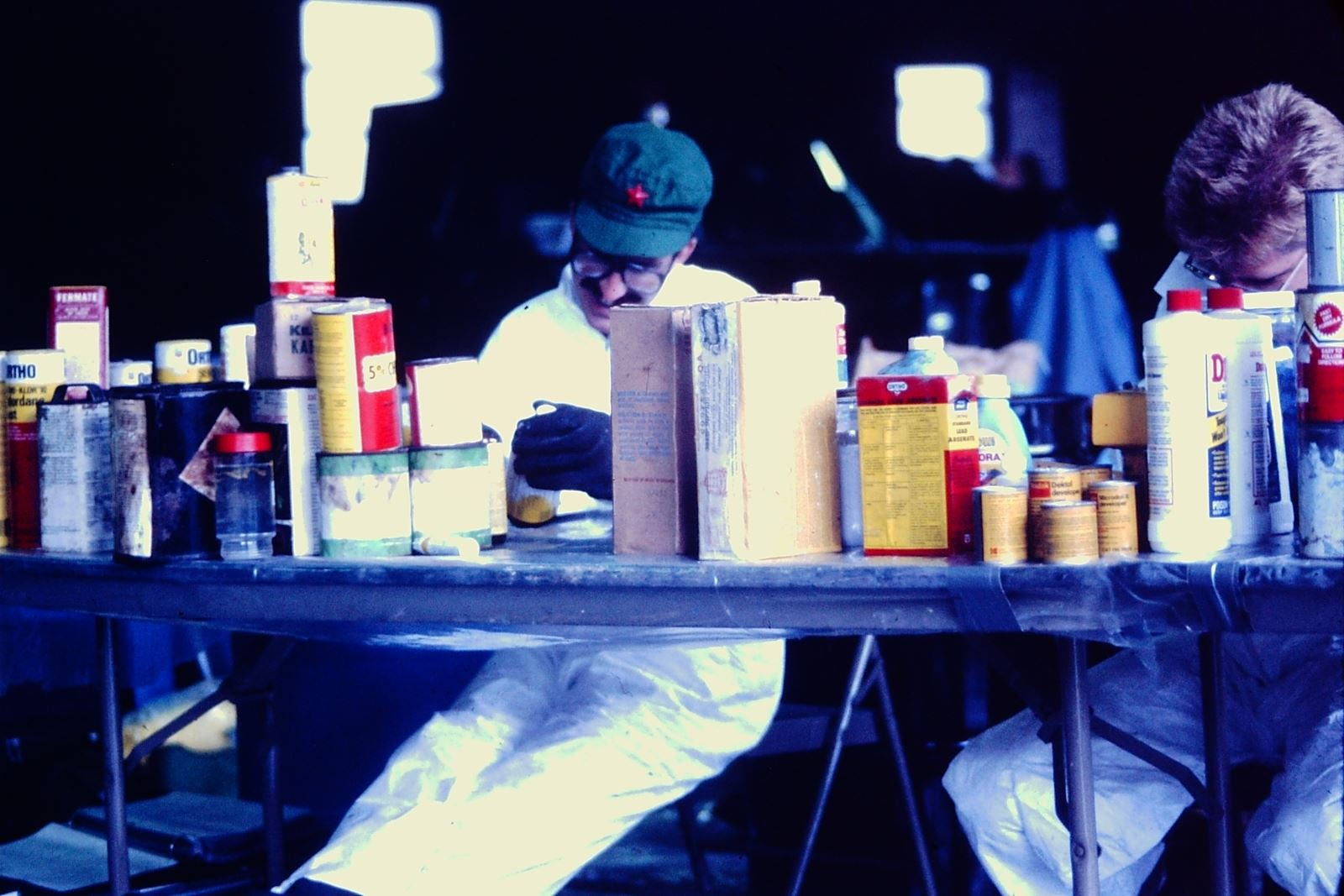 two people sitting behind a table covered in containers of hazardous materials